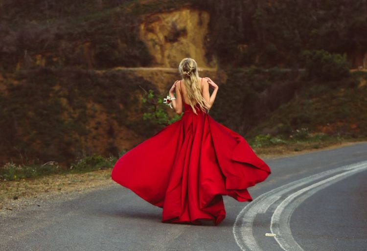 Full Length Of Young Woman In Red Evening Gown Walking On Road