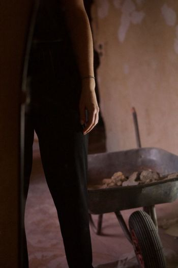 Midsection of woman standing by wheelbarrow