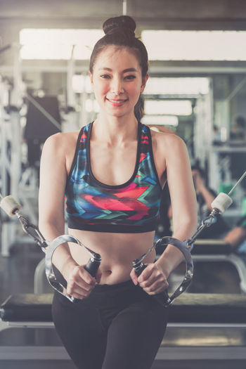 Portrait of smiling woman exercising in gym