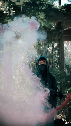 Portrait of young man holding smoke bomb