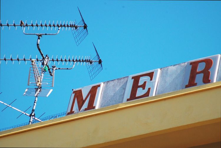 La mer Building Exterior Built Structure Architecture Low Angle View No People Text Outdoors Day Clear Sky Technology Sky Sixties '60 60's Mer La Mer Yellow Yellow Building Building Signboard Red Antennas Antenna Aerial Aerials