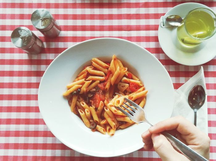 Cropped image of person having pasta served on table