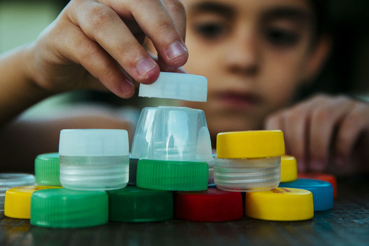 Boy playing with bottle caps on table