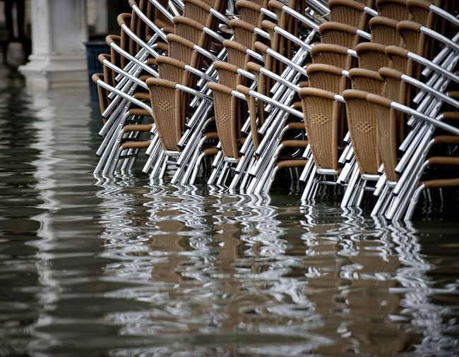 Brown stacked chairs on water filled walkway during flood at piazza san marco