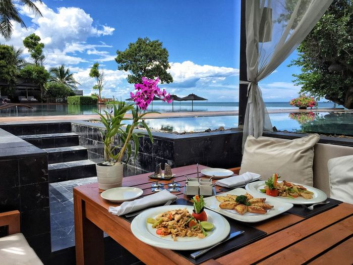 Seafood served in plates on table by infinity pool at hotel