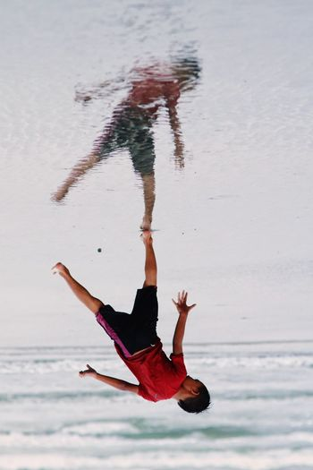 Upside down image of boy standing on shore at beach