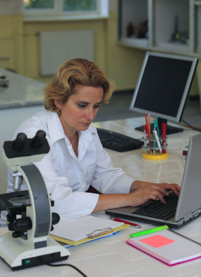 Female researcher working on a laptop at her workplace in a laboratory. Technology Computer Laptop One Person Connection Using Laptop Adult Occupation Desk Lab Coat Female Researcher Researcher Life Female Researcher Lab Laboratory Scince Scientist Education Studying University Chemistry Medical Research Medical Researcher