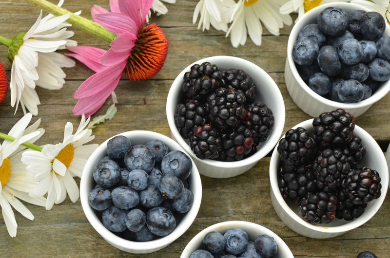 Blueberries and blackberries in small white ramekin with garden daisies on rustic wood table