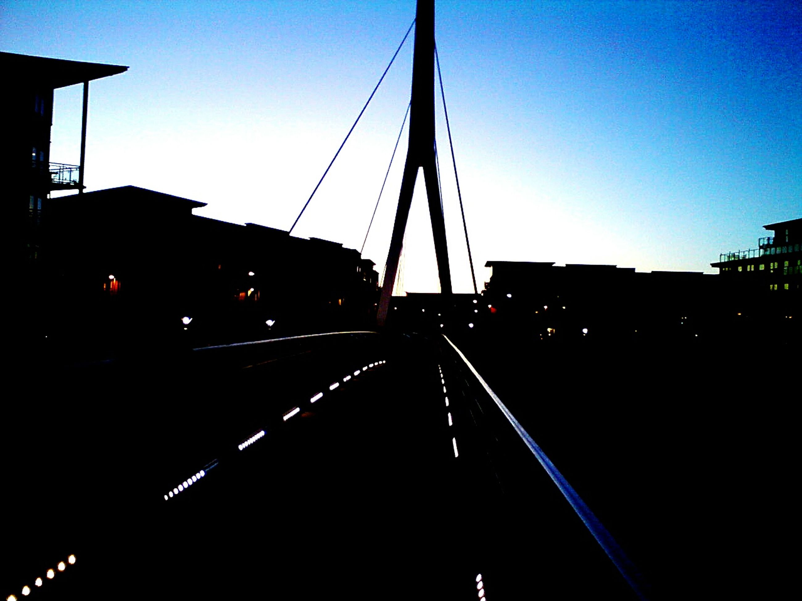 transportation, connection, clear sky, the way forward, built structure, architecture, railroad track, sunset, dusk, diminishing perspective, silhouette, sky, illuminated, blue, vanishing point, bridge - man made structure, copy space, rail transportation, building exterior, outdoors