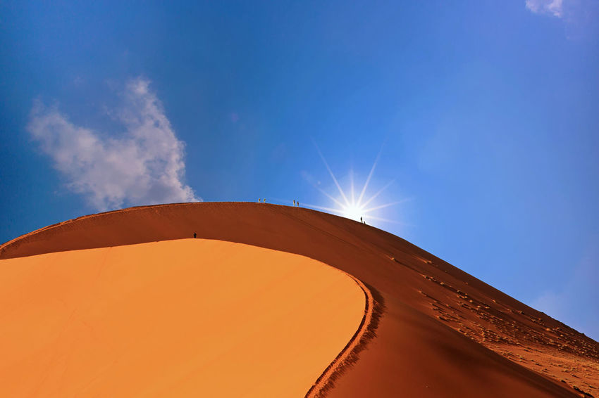 Snad dune in Namib Naukluft desert with people climbing, with the sun peeping over the top - Namibia , Southern Africa Beauty In Nature Blue Blue Sky And Clouds Climbing Day Dunes Hiking Hot Low Angle View Namib Desert Namib Naukluft National Park Namibia Namibia Landscape Nature Outdoors Sand Sand Dune Sesriem, Namibia Sky Sossusvlei Southern Africa Sunlight Sweltering Temperature Connected By Travel Go Higher