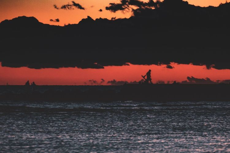 Silhouette person by sea against sky during sunset