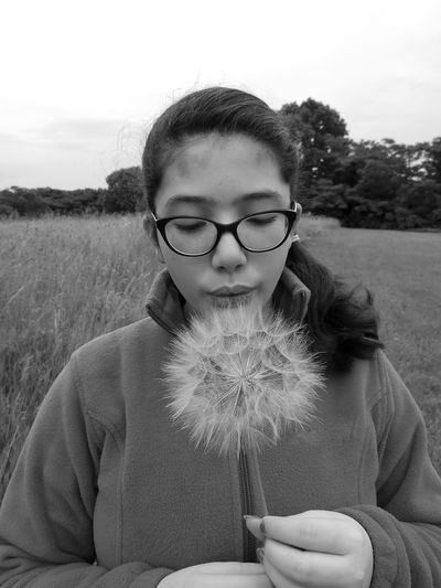 Close-up of teenage girl blowing dandelion while