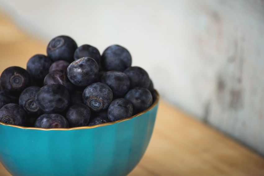 Blueberries in a blue bowl on wood table conceptual healthy antioxidant superfood simplicity background with room for copy Healthy Snack Breakfast Blueberry Fruit Food And Drink Indoors  Food No People Bowl Healthy Eating Freshness Close-up Day