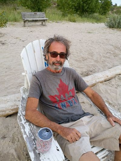 Man wearing sunglasses while sitting on chair with drinking can at beach