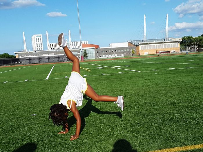 Cheerleader practicing cartwheel at american football field