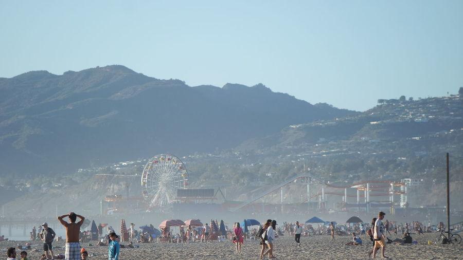People At Sandy Beach Against Clear Sky