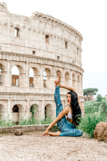 Woman sitting on historical building