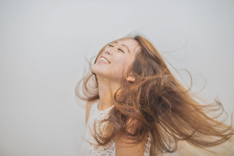 Cheerful young woman with tousled long brown hair against white background