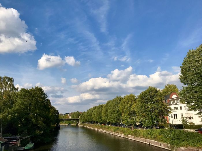 River amidst trees and buildings against sky
