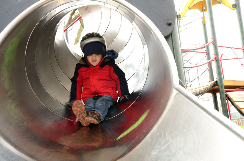 A young child playing in the childrens playground in Prospect Park in Reading, Berkshire. Berkshire Boy Child Childhood Children Close-up Fun Happy Leisure Activity Lifestyles Metal Metalic Outdoors Outside Person Play Portrait Prospect Park Reading Red Coat Relaxing Slide Tube Tubular Young