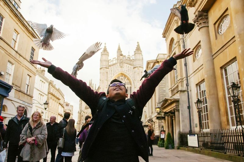 Man raising arms while birds flying against church