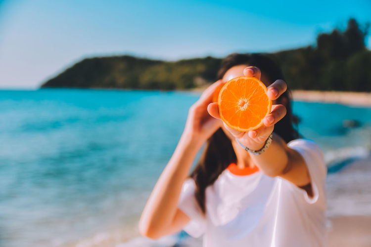 Young woman holding orange fruit at beach
