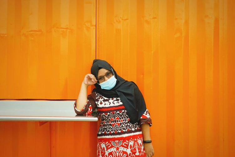 Portrait of woman wearing mask standing against orange wall