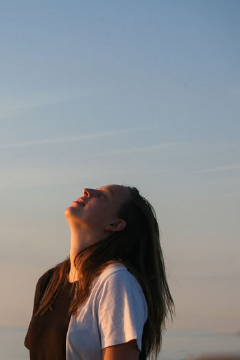 Side view of woman looking away against clear sky