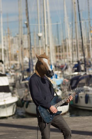 Man wearing horse mask while playing guitar at harbor