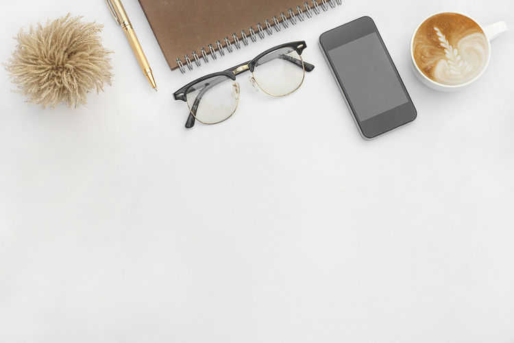 office white desk top view. Business Classroom Coffee Copy Space Desk Education Eyeglasses  No People Note Notebook NotePad Office Paper Pencil School Screen Smartphone Supplies Table White Background