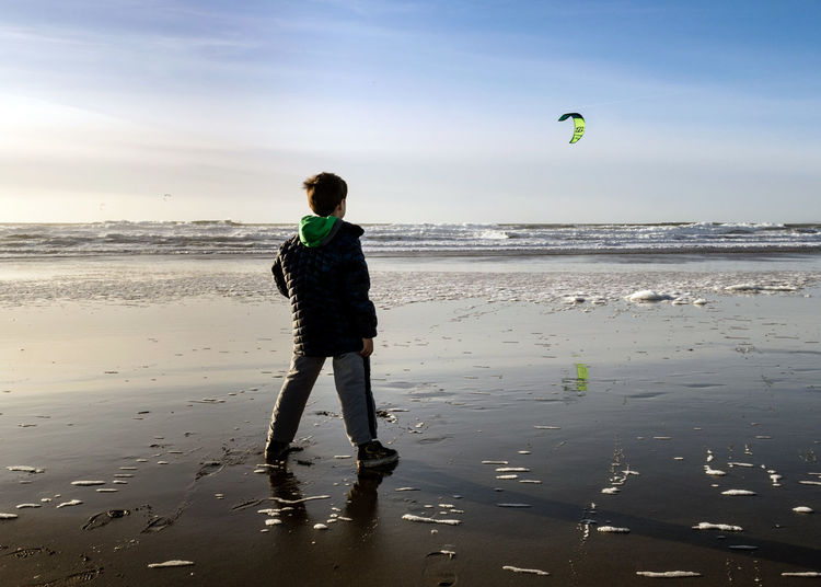 Rear view of boy looking at kite flying over sea
