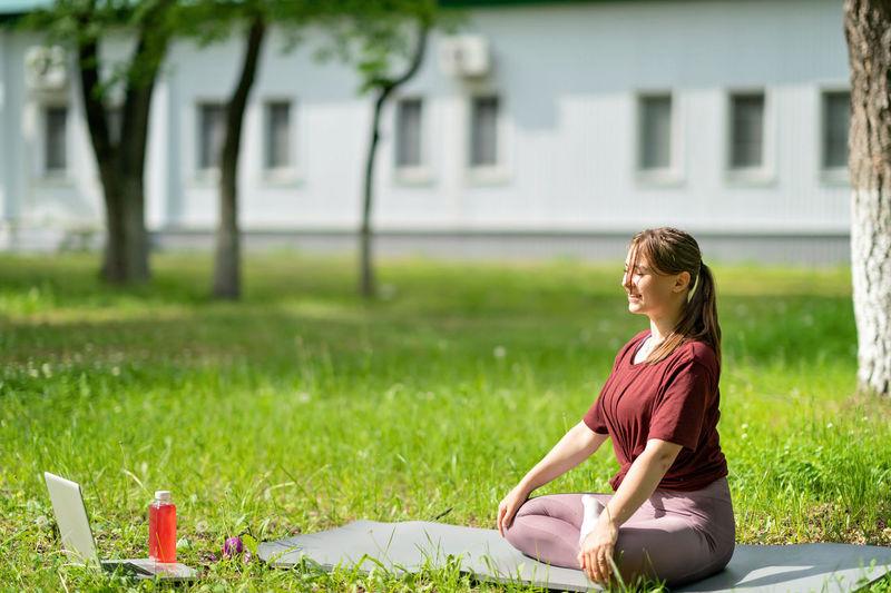 Woman sitting on field against plants