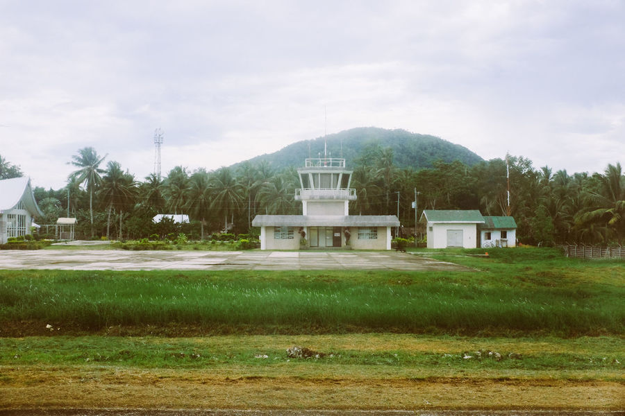 Airport tower with jungle in the background Airport Architecture Cloud - Sky Day Government Jungle Nature No People Outdoors Politics And Government Runway Sky Tower Transportation Tree Water