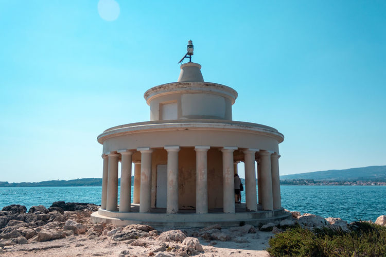 Lighthouse of saint theodoroi Sky Architecture Sea Nature Water Built Structure Architectural Column Building Exterior Clear Sky No People Day Land The Past History Travel Destinations Religion Blue Beach Building Outdoors