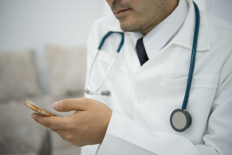 Midsection Of Doctor Holding Smart Phone