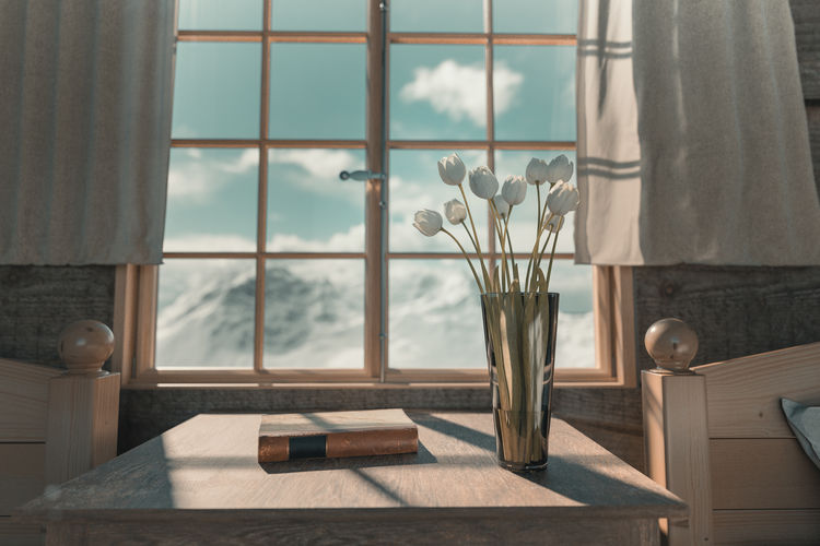 Flower vase and book on table by window at home