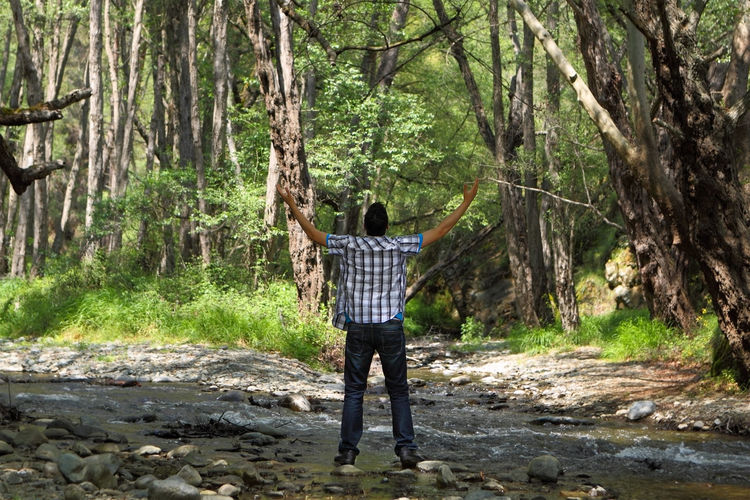 Man in Forest with Arms Lifted Up Man Male Guy Teenager Christian Christianity Prayer Meditate Religion Faith Born-again Spirituality Worship Praise Alone God Solitude Creek Water Celebrate Forest Woods Victory Overcome Winner Breakthrough Happy Joy Rejoice Rejoicealways
