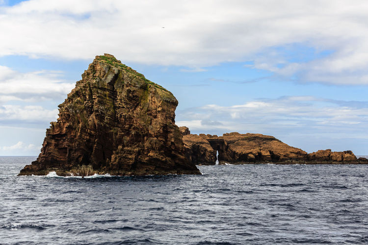 Rock formations in sea against sky