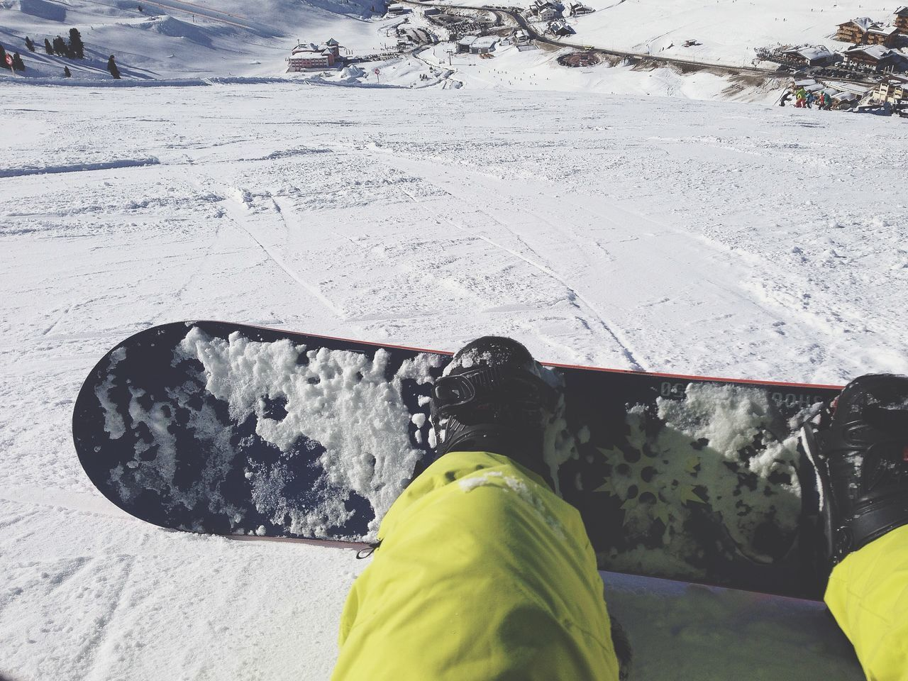 Close-up of snowboarder sitting on snow covered landscape