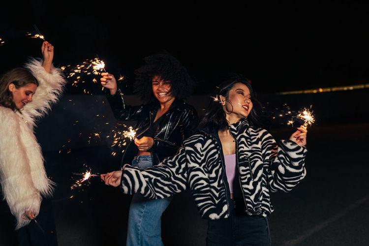 Smiling women holding sparkler enjoying outdoors at night
