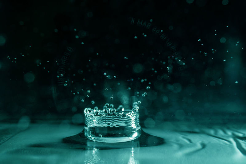 Close-up of splashing droplet in blue water against black background