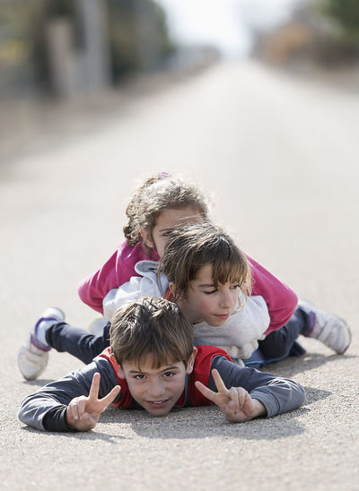 Three children lying on the floor one on top of the other. Horizontal shot with natural light Children Children's Portraits Spanish Tree Children Caucasian Ethnicity Child Childhood Day Friendship Girls Leisure Activity Lifestyles Looking At The Camera Outdoors People person Playing Real People Smiling Togetherness