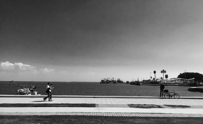 Side view of people walking against the sea