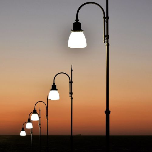 Illuminated street lights against clear sky during sunset