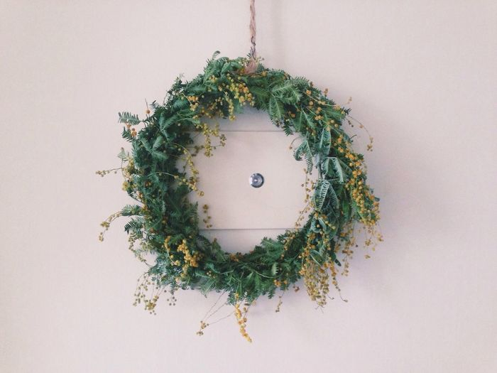 Close-up of wreath and peephole on white door