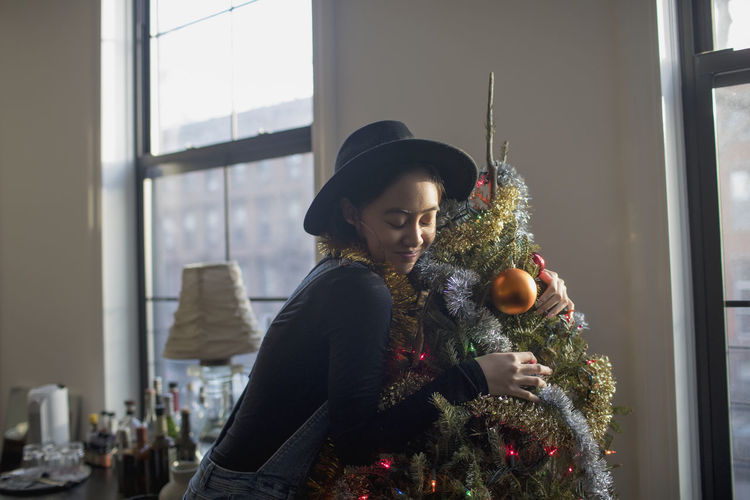 Woman with christmas tree at home