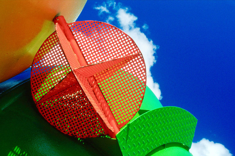 Low angle view of colorful metallic built structure against blue sky