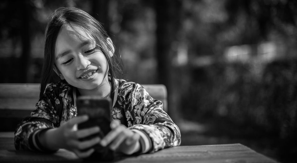 The Portraitist - 2017 EyeEm Awards Asian Girl Kid Sitting Outdoor Child Nature Elementary Age Childhood Leisure Activity Sitting Outside Smiling Mobile Phone Leisure Activities Portrait Asian  Children Young Girl Long Hair Laughing Happy