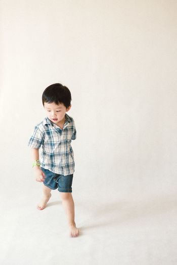 Cute little Asian boy Child Full Length Childhood Males  Boys Standing Portrait White Background barefoot Casual Clothing Toddler  Preschooler