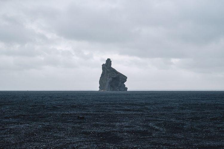 A rock formation in Hjörleifshöfði, Iceland. Sky Cloud - Sky Sea Horizon Horizon Over Water Water Nature Scenics - Nature Tranquil Scene Beauty In Nature Tranquility No People Land Rock Solid Overcast Rock Formation Rock - Object Stack Rock Hjörleifshöfði Iceland